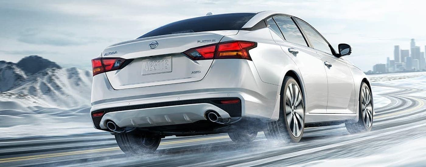 A white 2021 Nissan Altima is shown from behind while driving on a snowy road towards a city.