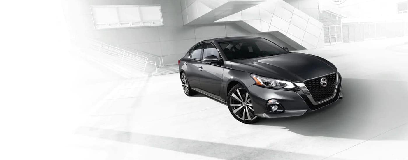 A gray 2021 Nissan Altima is on a washed out background image of a building with stairs.