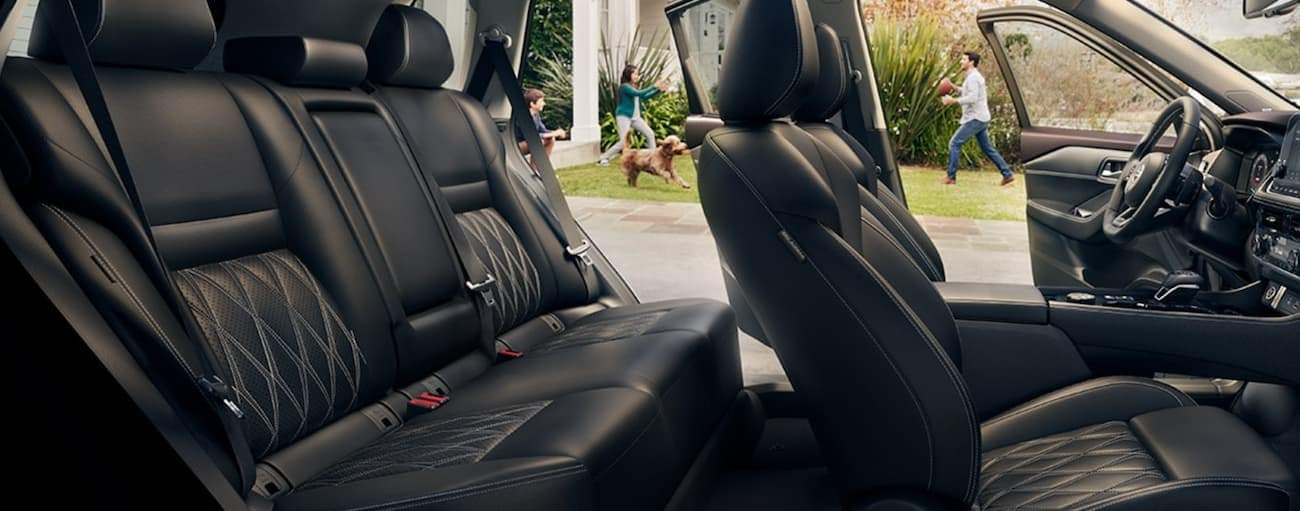 The black interior of a 2021 Nissan Rogue is shown with the doors open and a family playing outside.