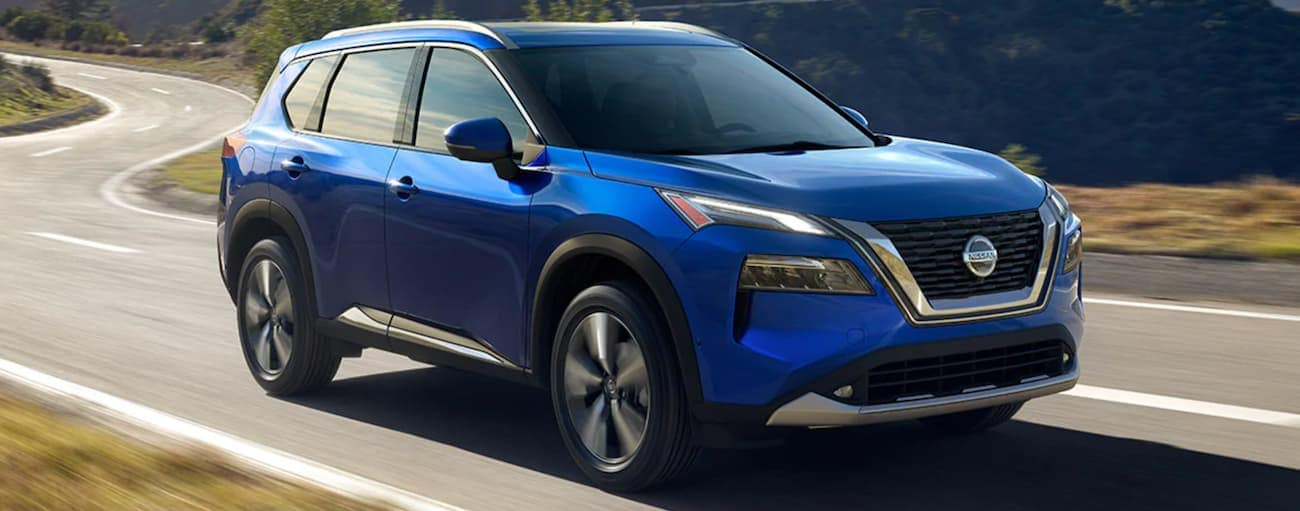 A blue 2021 Nissan Rogue is driving on a winding mountain road.