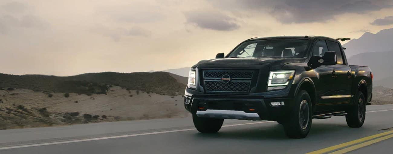 A black 2021 Nissan Titan is driving on a highway at sunset.
