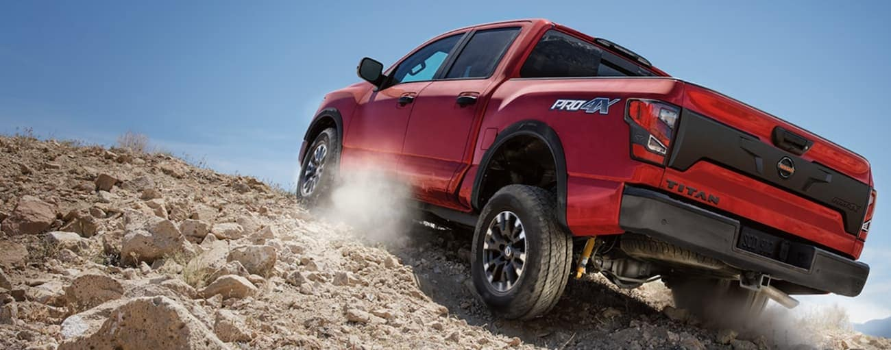 A red 2021 Nissan Titan Pro4X is off-roading up a dirt hill.