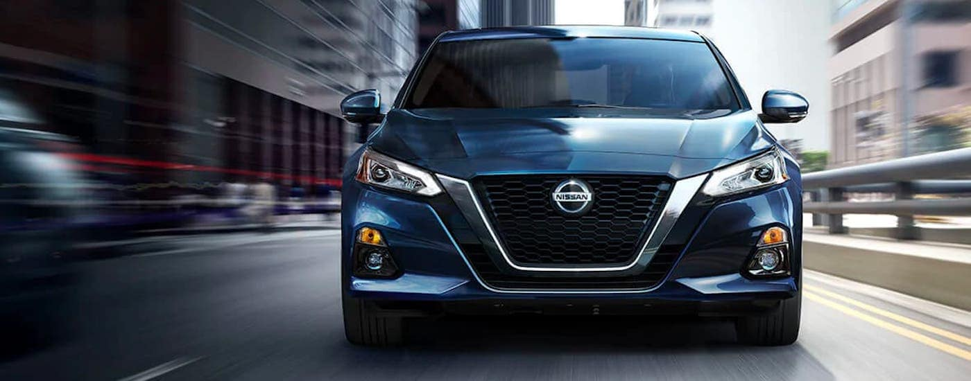 The front of a blue 2021 Nissan Altima is shown driving in a city.