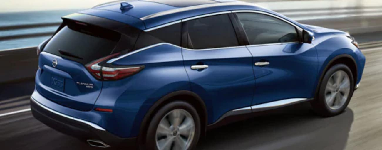 A blue 2020 Murano, similar to the 2021 Nissan Murano, is shown driving from a rear-side angle.