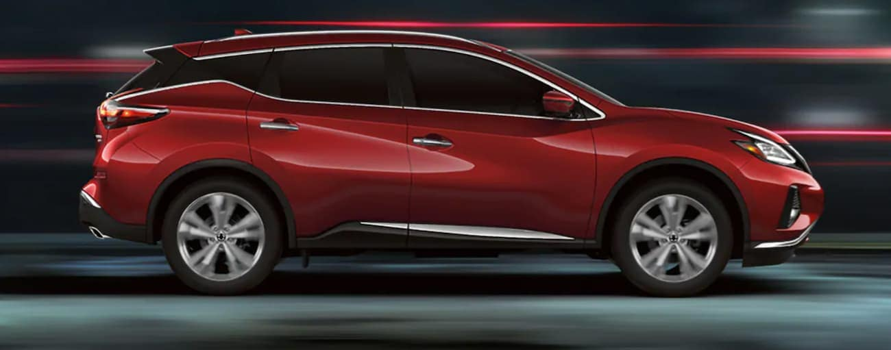 A red 2020 Murano, similar to the upcoming 2021 Nissan Murano is drivign past blurred lights, shown from the side.