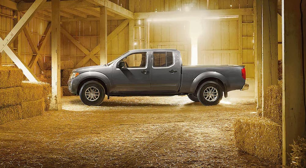 A grey 2021 Nissan Frontier is shown from the side, parked in a barn near hay bales.