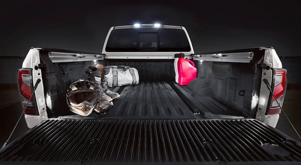 A close up is shown of the bed with dirt bike equipment on a white 2021 Nissan Titan.