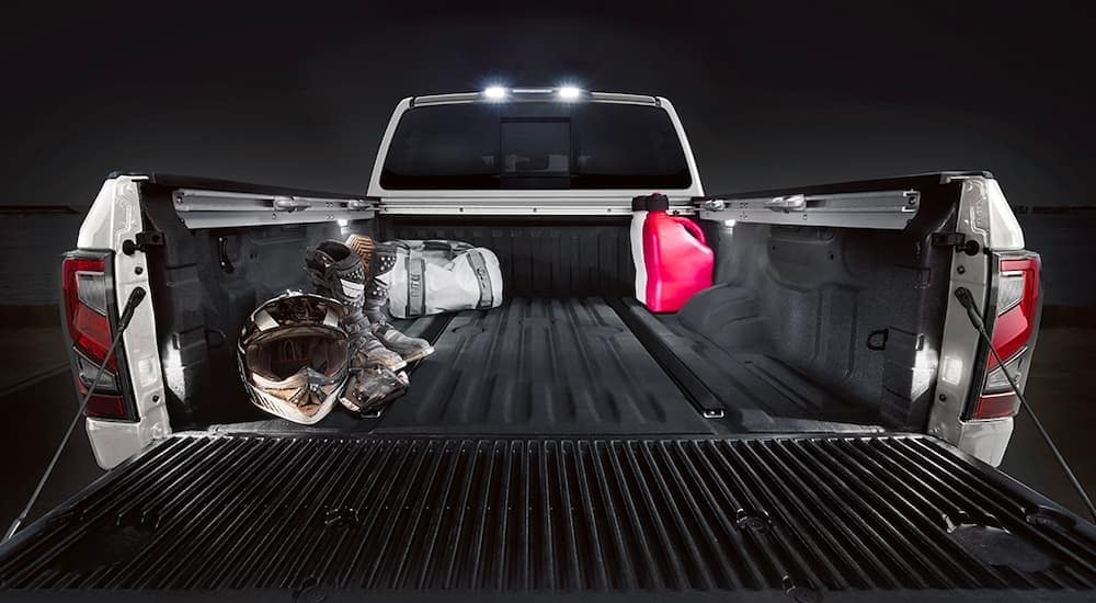 A close up is shown of the bed and dirt bike equipment on a white 2021 Nissan Titan.