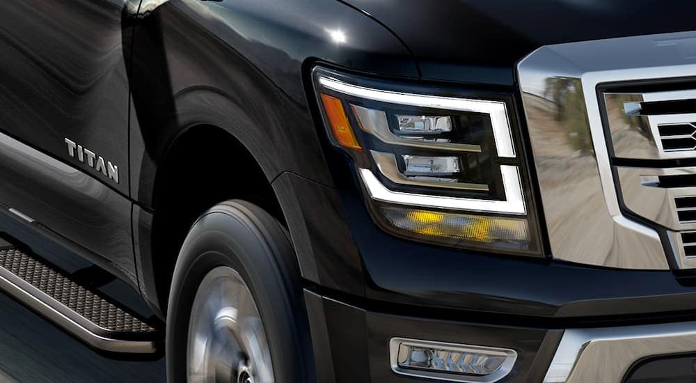 A close up is shown of the LED passenger headlight on a black 2021 Nissan Titan.