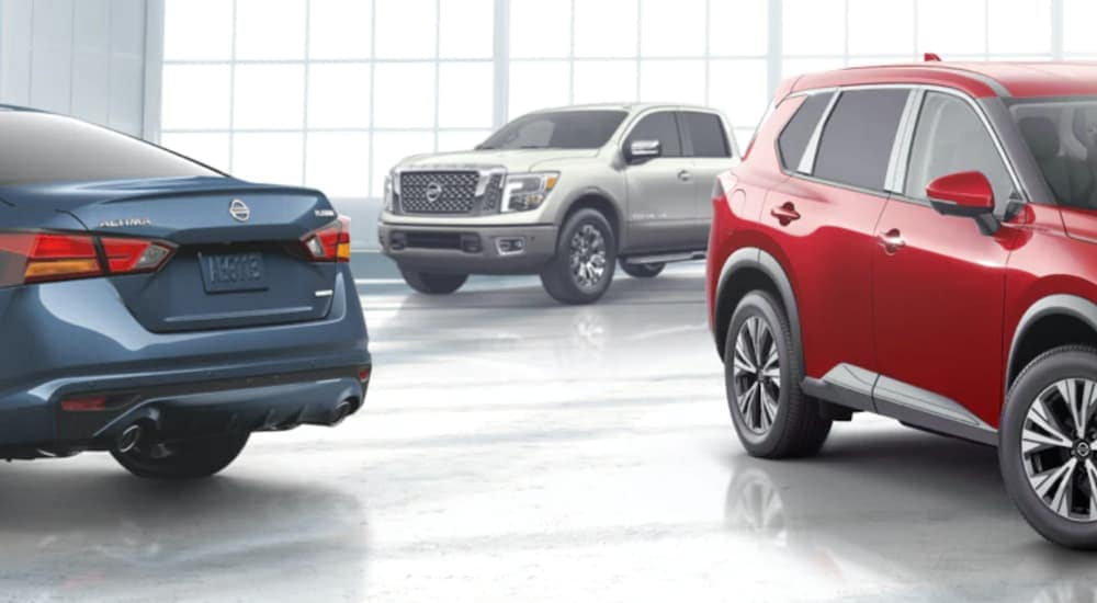 A blue car, red SUV. and White 2021 Nissan Titan are in a Tullahoma Nissan dealer.