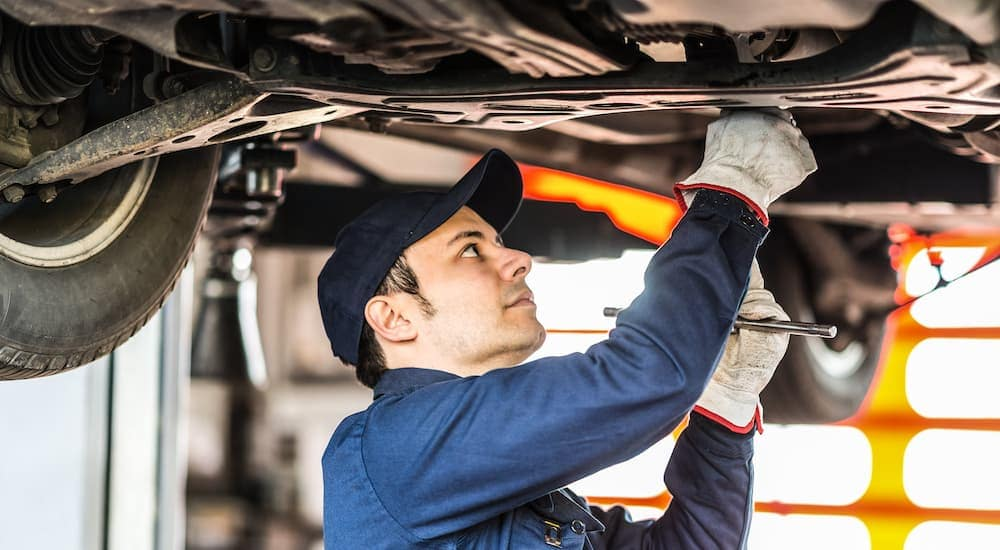 A mechanic is working under a vehicle.