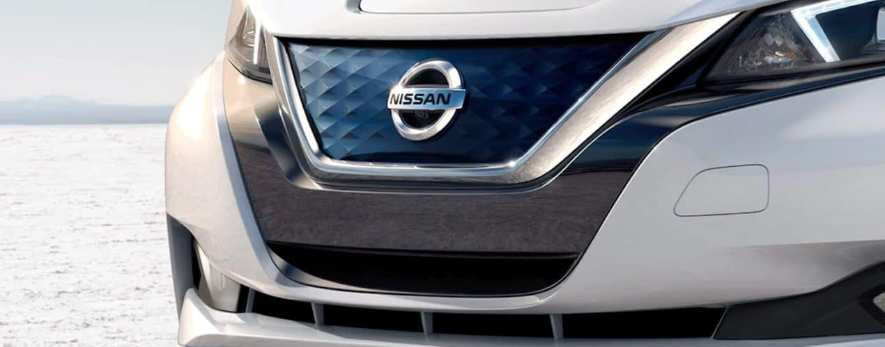 A close up shows the front grille and headlights of a white 2021 Nissan LEAF.