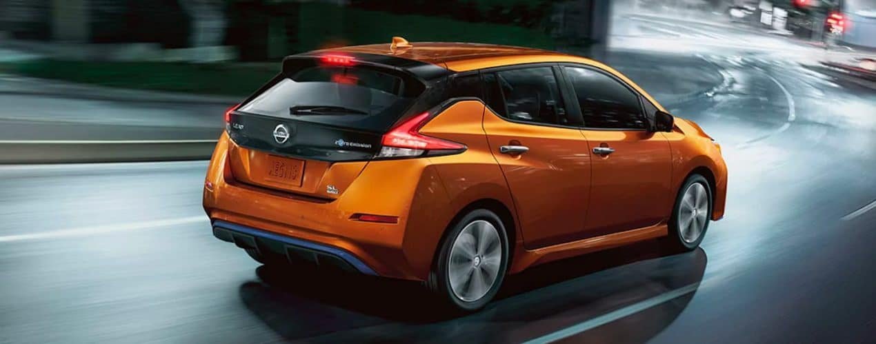 An orange 2021 Nissan LEAF is shown from the rear driving down wet pavement in the city.