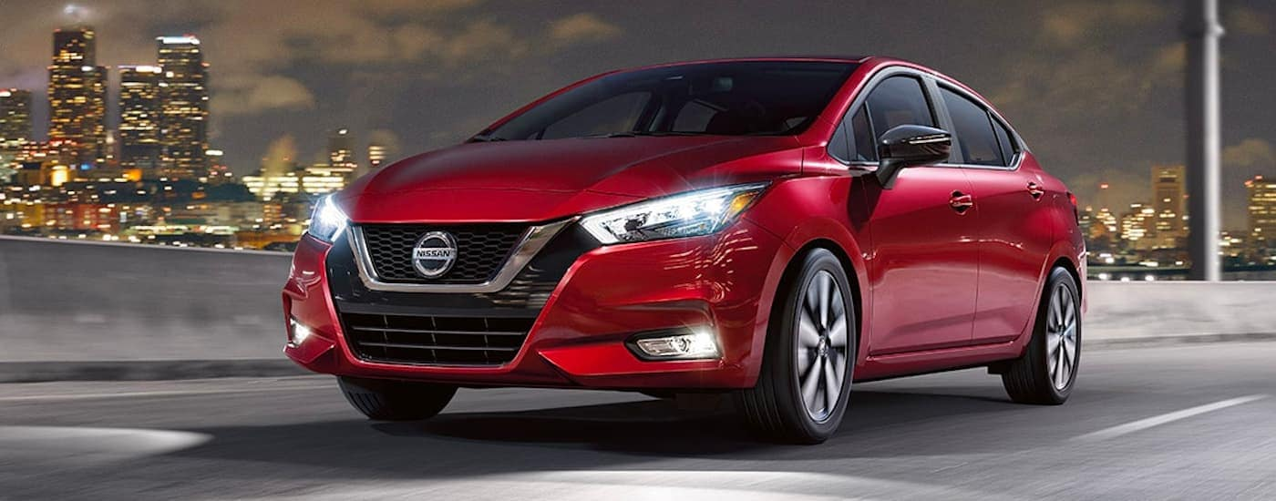 A red 2021 Nissan Versa is shown driving through a city at night.