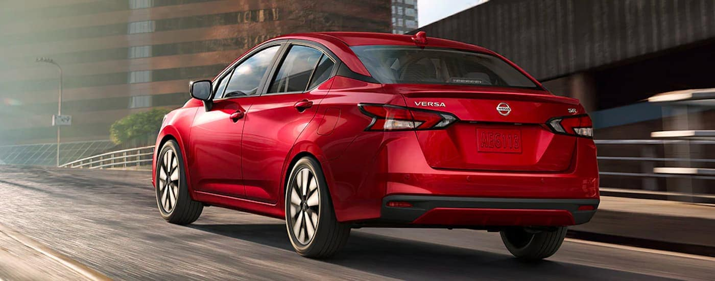 A red 2021 Nissan Versa is shown from the rear driving down a city street.