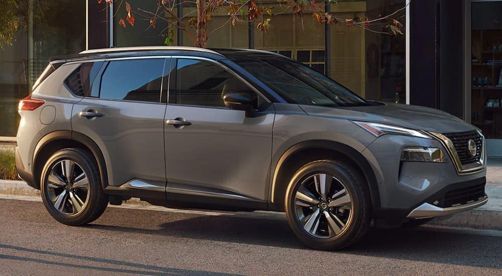 A grey 2021 Nissan Rogue is parked on a city street at sunset.