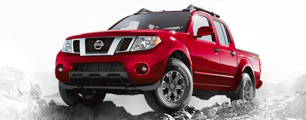 A red 2021 Nissan Frontier is shown parked on top of a rocky path.