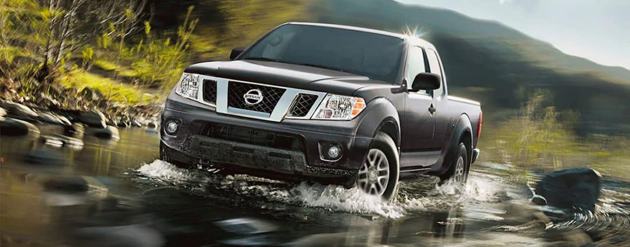 A dark gray 2021 Nissan Frontier is driving through a river.