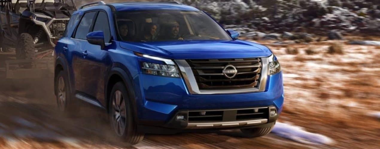 A blue 2022 Nissan Pathfinder is towing a side by side on a dirt road with some snow.
