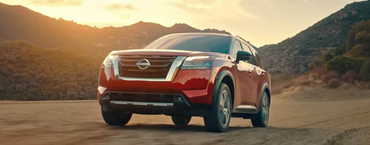A red 2022 Nissan Pathfinder is driving on a dirt road past hills at sunset.