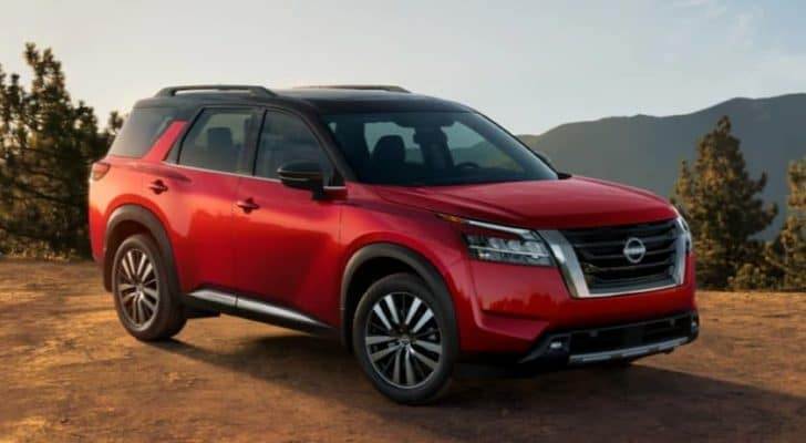 A red 2022 Nissan Pathfinder is angled right in front of mountains.