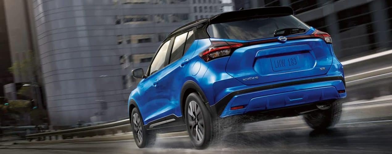 A blue 2021 Nissan Kicks is driving on a wet city street.