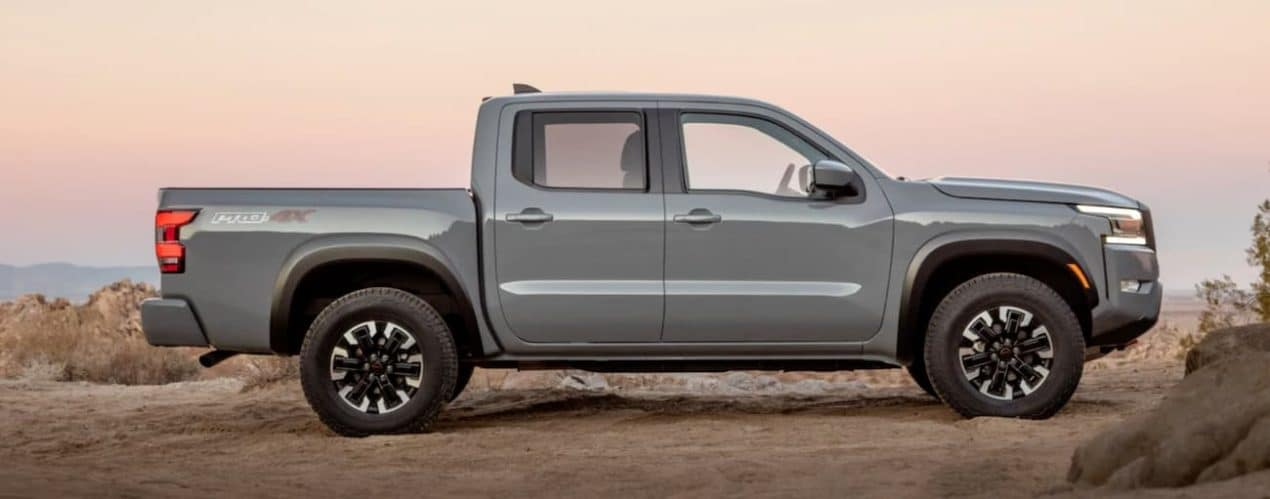 A grey 2022 Nissan Frontier is shown from the side at sunset.