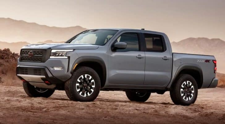 A grey 2022 Nissan Frontier is parked in front of desert mountains.
