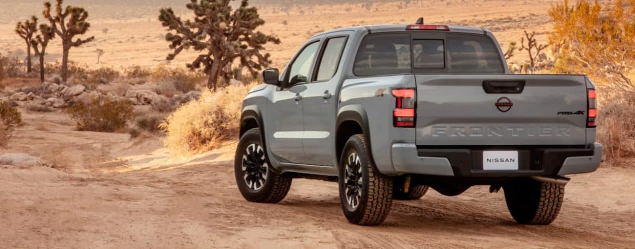 A grey 2022 Nissan Frontier is parked in the desert shown from the rear.