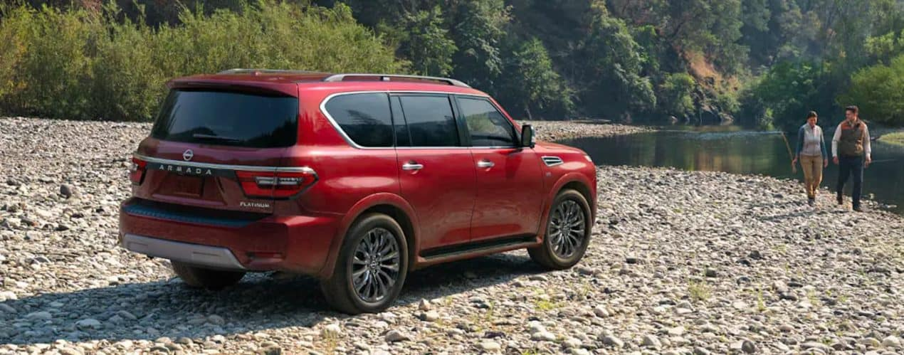 A red 2021 Nissan Armada is shown parked on a rocky river bed next to a couple with a fishing rod.