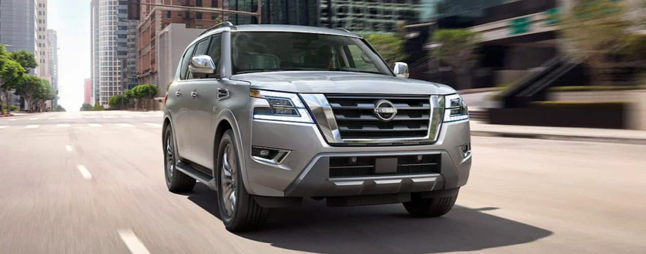A silver 2021 Nissan Armada is shown from the front driving through the city.