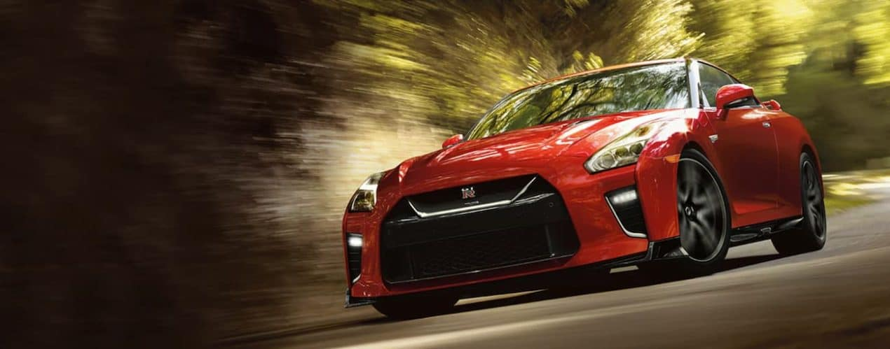 A red 2021 Nissan GT-R is driving on a road past blurred trees.