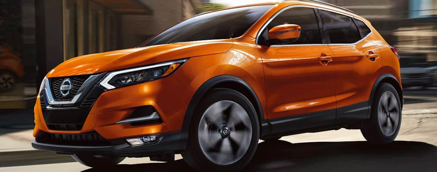 An orange 2021 Nissan Rogue Sport is shown from the side driving down a city street.