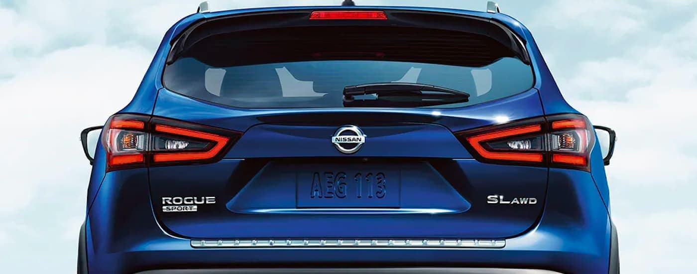 A close up shows the rear badging and taillights on a blue 2021 Nissan Rogue Sport SL.