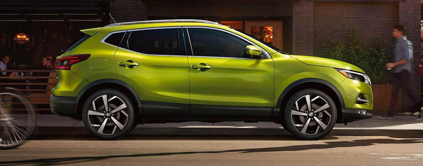 A bright green 2021 Nissan Rogue Sport is shown from the side parked on a city street.