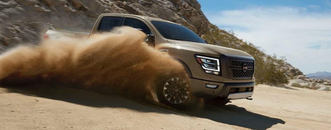 A tan 2021 Nissan Titan XD Pro-4X is off-roading in sand.