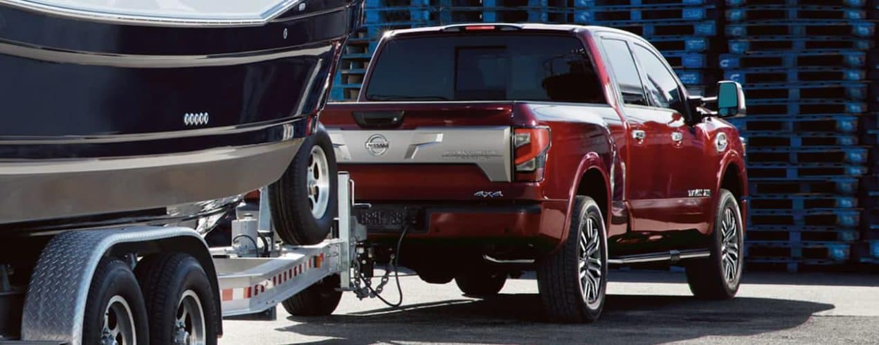 A red 2021 Nissan Titan XD is shwon from the rear towing a boat in front of blue pallets.