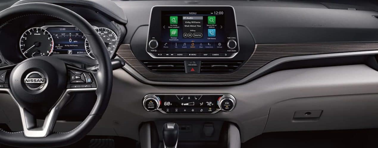 The interior of a 2021 Nissan Altima shows the steering wheel and infotainment screen.