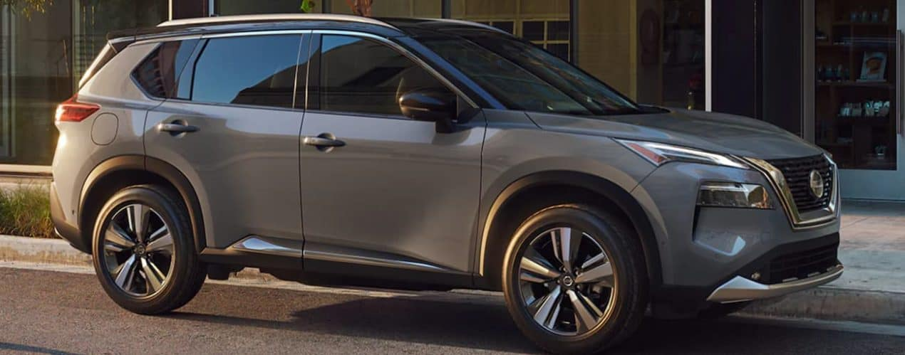 A grey 2021 Nissan Rogue is parked on a city street.