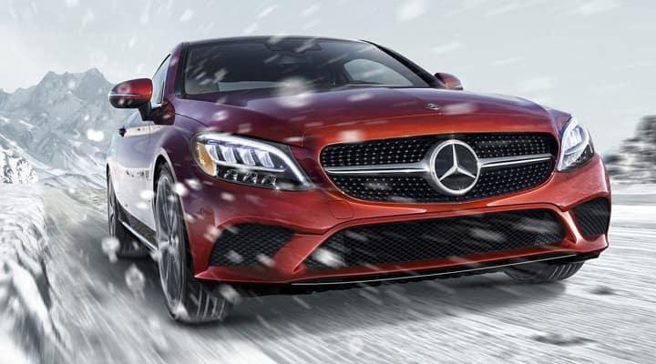 Red Mercedes-Benz sedan driving through snow