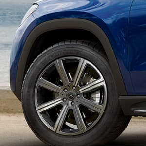 Close up view of the driver site front wheel on a blue Mercedes-Benz SUV