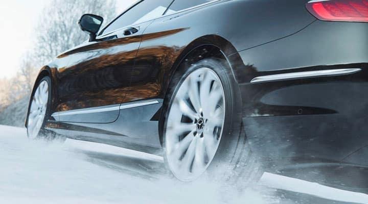 Black Mercedes-Benz sedan driving through snow