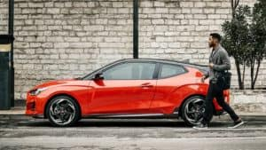 2021 Hyundai Veloster in red with man walking