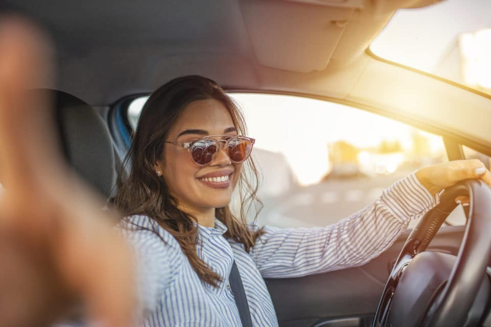 Smiling young woman wearing sunglasses sitting behind the wheel of her new car