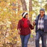 couple walking through wooded trail in autumn