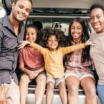 Family of five sitting on back of SUV