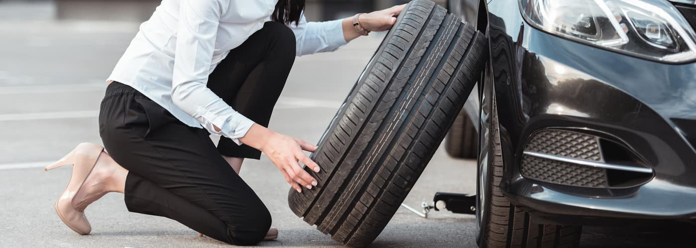 Woman putting on spare tire_168217334
