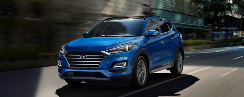 Blue Hyundai Tucson driving in city