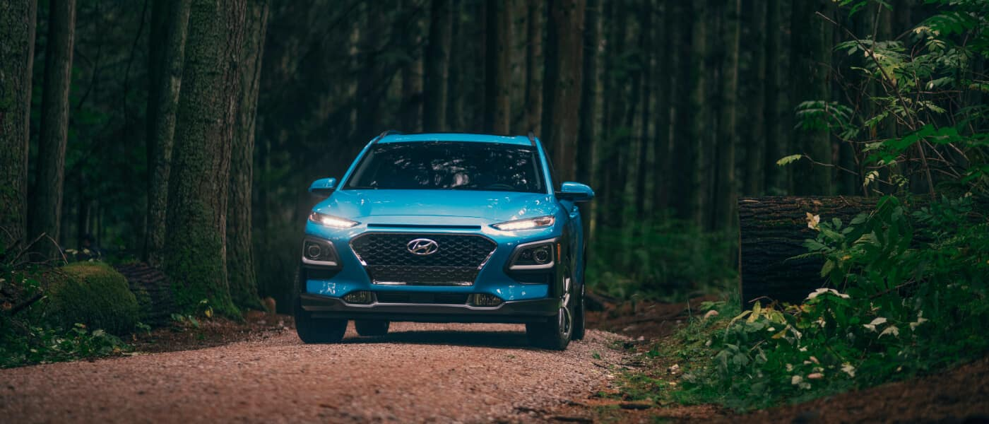 A blue 2020 Hyundai Kona driving through the forest