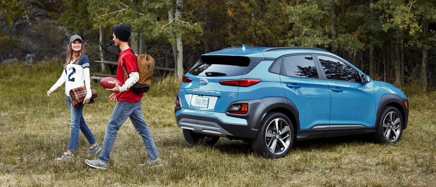 A couple walking away from a blue Hyundai Kona
